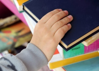 Kid's Hand Taking Book from a Shelf in Public Library.