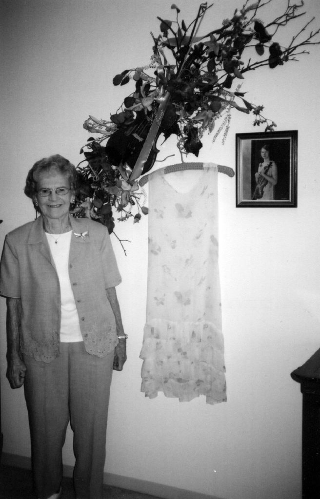 Photo by Julie Schrader - Muriel Kuebler Berndt in 2004, standing next to her violin (which was made into a floral arrangement for her wall), one of her original dance dresses and an old photograph of herself with the violin.