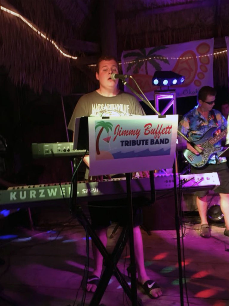 Submitted Image – Garrett Steinberg in front of the Jimmy Buffett Tribute Band, one of his many musical incarnations.